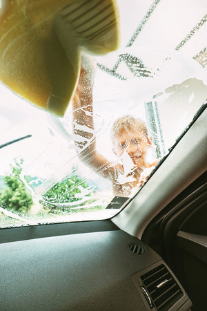 Little Boy washing front car window with soap foamy sponge. Inside car camera view.
