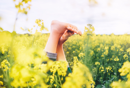 Legs up of happy female lying in deep yellow flowers meadow. Happiness in nature concept image.