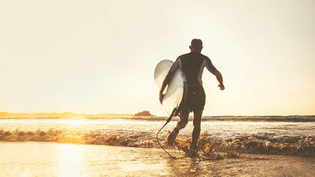 Young man Surfer taking surfboard and running with long surf board to waves on the evening sunset sky Stock Photo