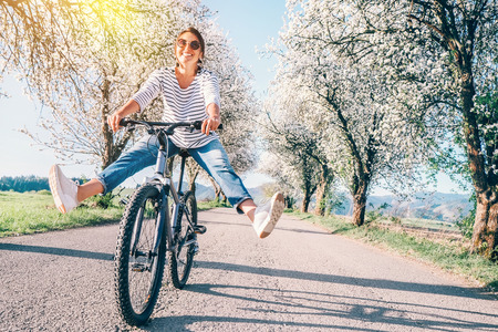 Happy smiling woman cheerfully spreads legs on bicycle on the country road under blossom trees. Banco de Imagens