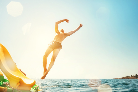 Man jumping backwards somersault into the sea. Happy beach vacation concept image. Stock Photo