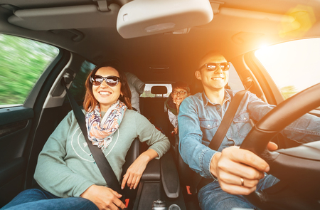 Young traditional family has a long auto journey and Cheerfully singing aloud the favorite song together. Safety riding car concept wide angle inside car view image. Banque d'images