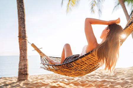 Young beautiful blonde longhaired woman relaxing in hammock hinged between palm trees on the sand beach