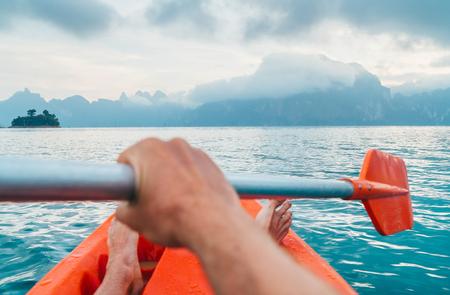 POV of Man floating in kayak holding paddle during early morning tour. Khao Sok national park, Cheow Lan lake, Thailand
