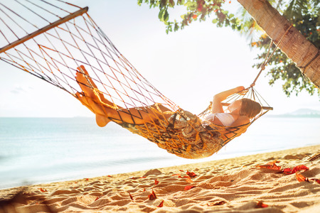 Young blonde longhaired woman relaxing in hammock hinged between palm trees on the sand beach