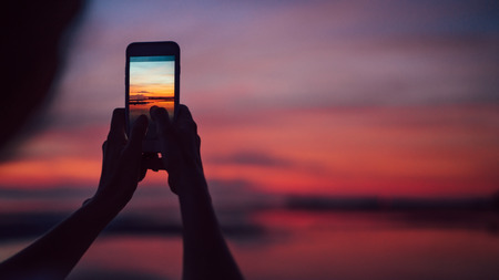 Close up hands with smartphine image of female making an incredible sunset snap shot