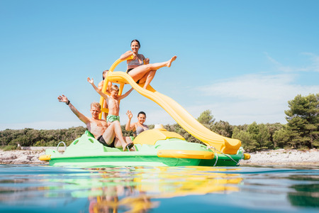 Happy family hands up on floating Playground slide Catamaran as they enjoying sea trip durins summer vacation