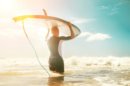 Young man Surfer taking surfboard on head and comming with long surf board to waves. Active holidays spending concept.