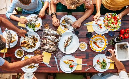 Großes Familienessen der Miltigeneration im Gange. Vertikales Bild der Draufsicht auf Tisch mit Essen und Händen