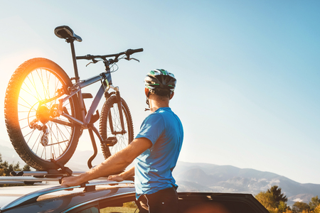 Man take his bicycle from car roof 스톡 콘텐츠