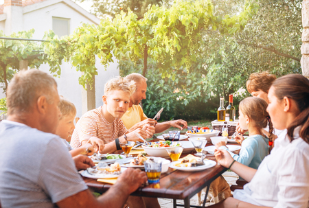 Big multigeneration family have dinner on open garden terrace Imagens