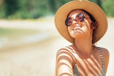 Happy smiling sun buthing woman in straw hat portrait. Palm tree shadows on the body. Health tanning concept