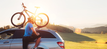 Man take his bicycle from car roof. Mountain biking concept