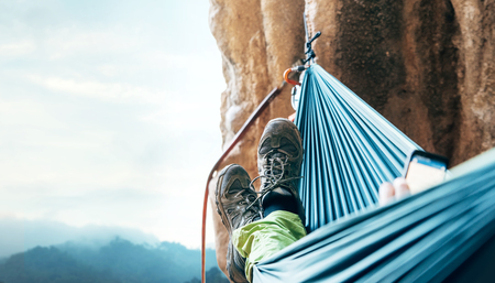 Climber resting in hammock on the vertical cliff wall