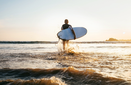 Young man Surfer taking surfboard and comming with long surf board to waves on the evening sunset sky background. Active holidays spending concept.