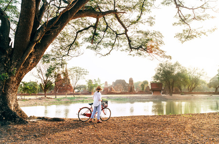 Female traveler weared light summer clothes and hat have early morning walk with bicycle near pond in Ayutthaya historical park,Thailand