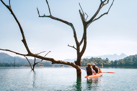 Mother and son travelers explore the Cheow Lan lake in Thailand