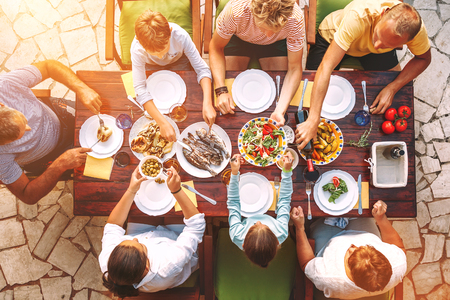 Big family have a dinner with fresh cooked meal on open garden terrace Stock Photo - 121462490