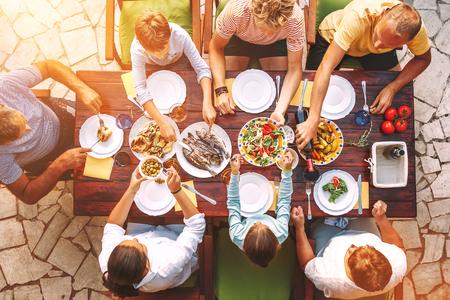 Gran familia tiene una cena con comida recién preparada en la terraza del jardín abierto