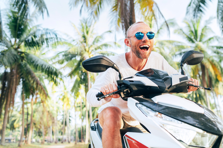 Happy smiling male tourist in sunglasses riding motorbike scooter during his tropical vacation under palm trees