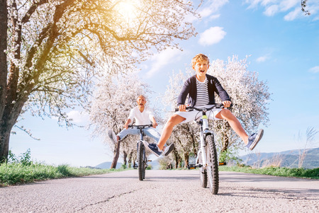 Father and son having fun spreading wide legs and screaming when riding bicycles on country road under blossom trees. Healthy sporty lifestyle concept image.