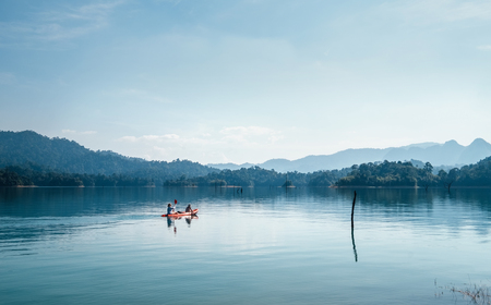 Mother and son floating on kayak together on calm water of Cheow Lan lake in Thailand