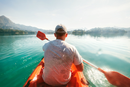 Teenager floating on kayak on calm water on Cheow Lan Lake, Khao Sok national park, Thailand Stock Photo - 121462618