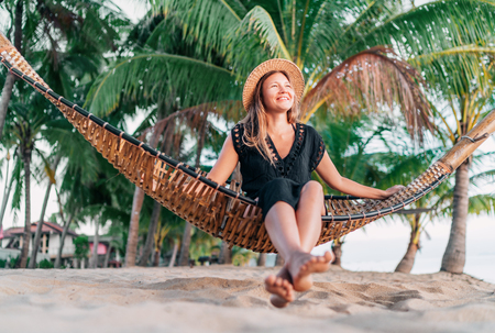 Positive young woman sitting in hammock on the tropical palm beach 版權商用圖片