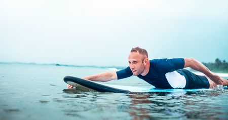 Man padding to line up on the surf board.  Active holidays spending concept. Stock Photo