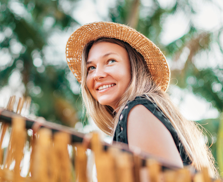 Positive young woman smiling sitting in hammock on the tropical palm beach