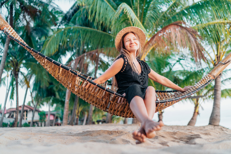 Positive young woman in straw hat swinging in hammock on the tropical beach