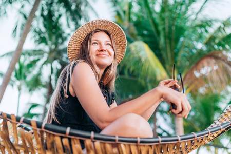 Happy smiling young woman in straw hat sitting in hammock with palm trees background