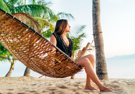 Lost in dreams girl sitting in hammock between palm trees on the tropical island beach