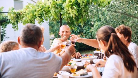 Family have dinner in summer garden 版權商用圖片
