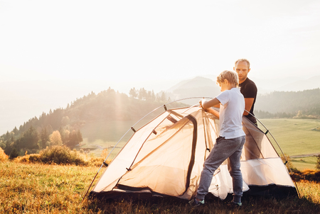 Father and son installing tent on forest glade.Trekking with kids concept image