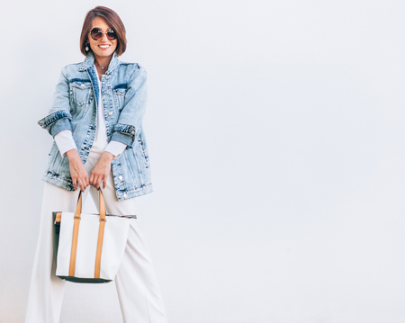 Elegant woman dressed in oversize denim jacket and wide white trousers Stockfoto