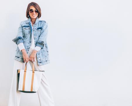 Elegant woman dressed in oversize denim jacket and wide white trousers 版權商用圖片