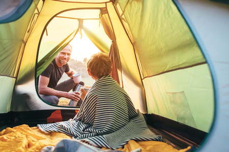 Family lisure concept image. Father and son prepare for camping in mountain, drink tea in tent 版權商用圖片