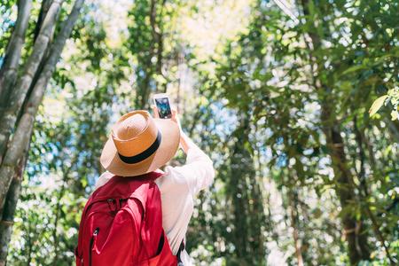 Donna con zaino in viaggio attraverso la foresta della giungla che smette di scattare foto con lo smartphone