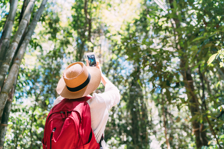 Woman with backpack on trek through jungle forest stopping taking picture with smartphone