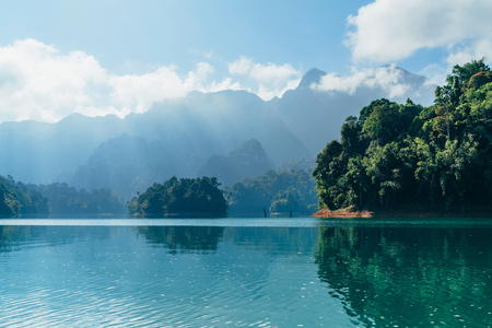 Incredible view of Cheow Lan lake with rainforest jungle on the banks with sun rays shining through white clouds. Surat Thani Province, Thailand.