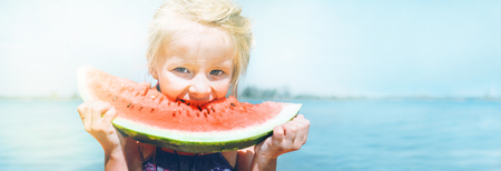 Little girl in pink sunglasses with big watermelon segment funny portrait. Healthy eating concept image. 版權商用圖片