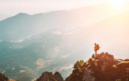 Excursionista de montaña con mochila pequeña figurilla permanecer en el pico de la montaña con un panorama de colinas impresionantes