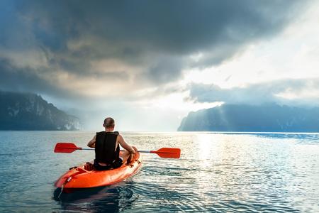 Man floating on kayak under sunrise sky on Cheow Lan Lake, Khao Sok national park, Thailand 版權商用圖片