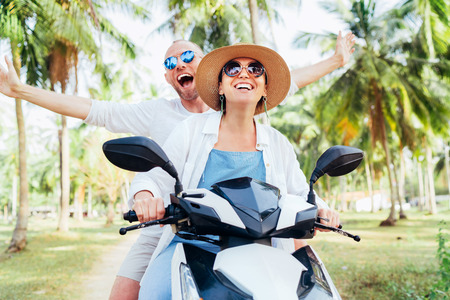 Happy smiling couple travelers riding motorbike scooter under palm trees. Tropical vacation concept image
