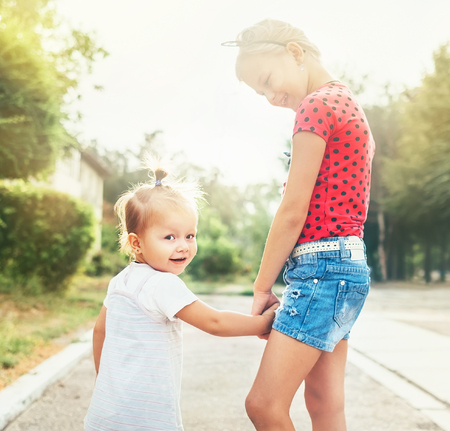 Two little sisters walking together in summer city park.
