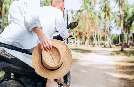 Happy woman riding motorbike with her boyfriend during their tropical vacation under palm trees Straw hat close up image