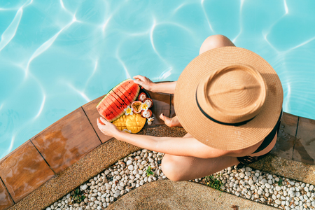 Top view of caucasian Woman in straw hat sitting on swimming pool side near plate of tropical fruits- camera and trying to eat watermelon.