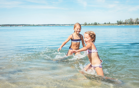 Two little sisters girls fooling around in the calm sea waves splashing water to each other. Family vacation concept image.