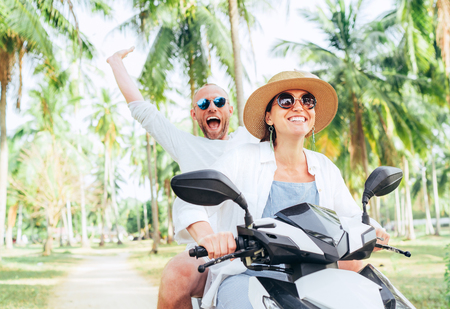 Laughing happy couple travelers riding motorbike during their tropical vacation under palm trees. Man emotionally raised hand up.